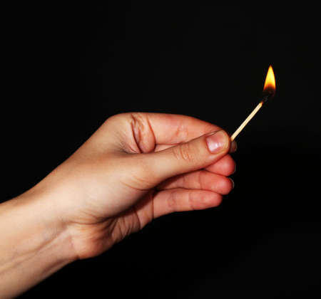 Burning match in hand on black background photo
