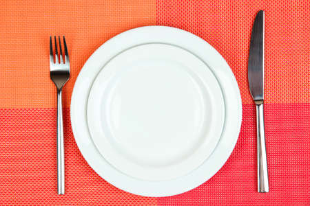 Knife, color plate and fork, on color background photo