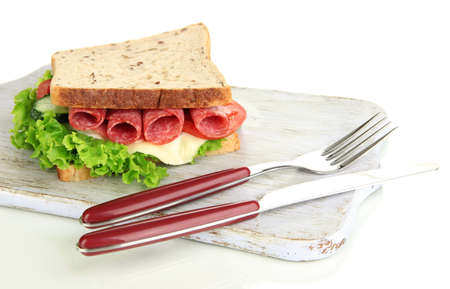 Tasty sandwich with salami sausage and vegetables on cutting board, isolated on white photo