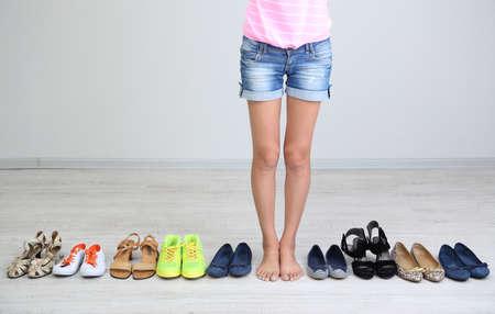 buying shoes: La muchacha elige los zapatos en la sala sobre fondo gris