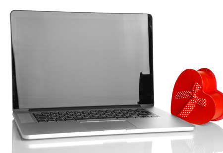 Laptop and gift isolated on white photo