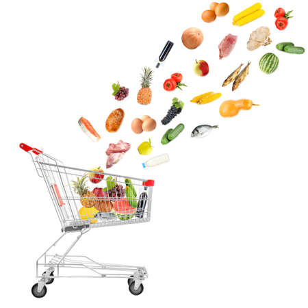 Food products flying out of shopping cart isolated on white