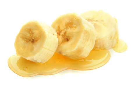 produce sections: Banana slices with honey, isolated on white