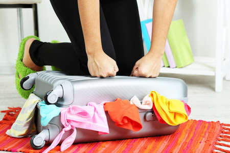 preparations: Suitcase with clothes on mat on room background Stock Photo