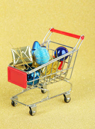 Christmas gifts in shopping trolley, on golden shiny background photo