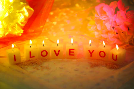 Candles with printed sign I LOVE YOU,on  color fabric background photo