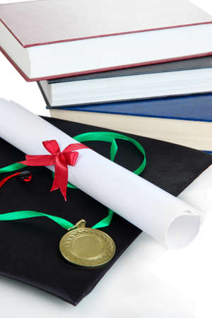 Medal for achievement in education with diploma, hat and books close up photo
