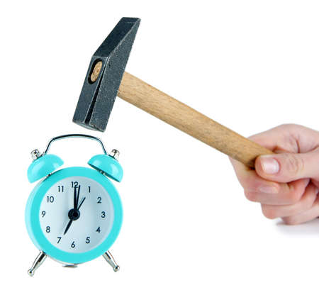 Hammer in hand and alarm clock isolated on white photo