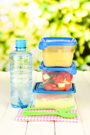 plastic spoon: Tasty lunch in plastic containers, on wooden table on bright background