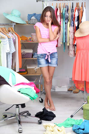 Beautiful girl thinking what to dress in walk-in closet Stock Photo - 23304762