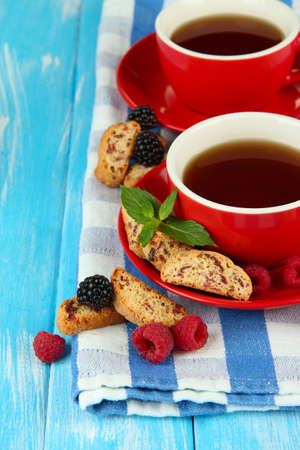 Cups of tea with cookies and berries on table close-up photo