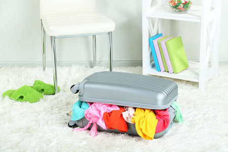 Suitcase with clothes on carpet on room background photo