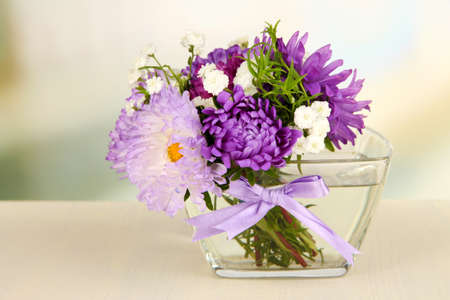 Beautiful bouquet of bright flowers in glass vase, on wooden table, on bright background photo