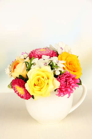 Beautiful bouquet of bright flowers in color mug, on wooden table, on  light background photo