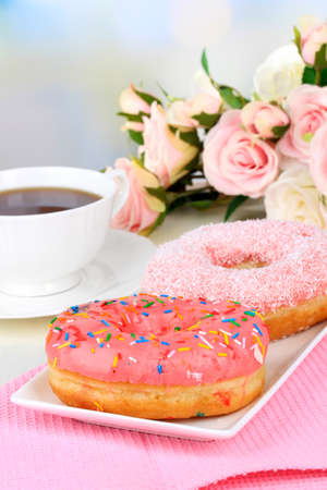 Sweet donuts with cup of tea on table on light background photo