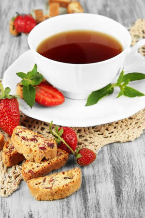 Cup of tea with cookies and strawberries on table close-up photo