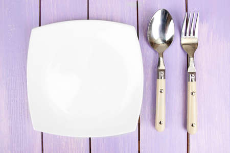 Plate and cutlery on wooden table close-up Stock Photo - 22968384