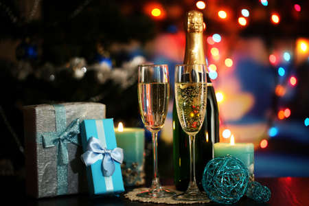 Glasses of champagne and gifts on bright background photo