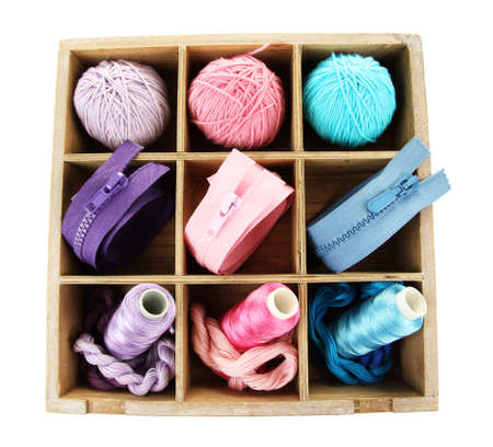 Multicolored skeins of thread and fasteners in box isolated on white photo
