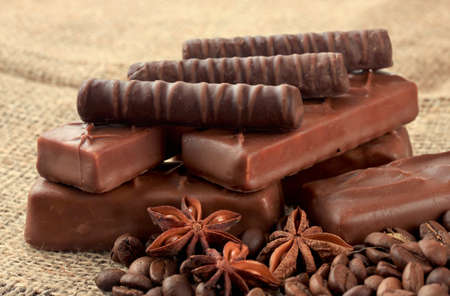 Delicious chocolate bars with coffee beans on sackcloth background Stock Photo - 22968525