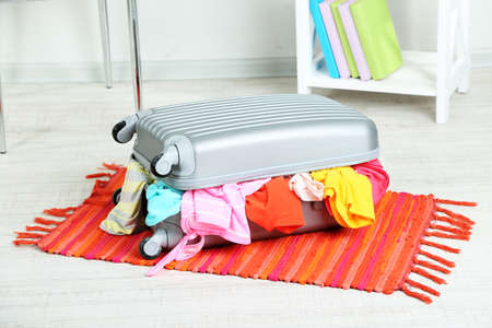 Suitcase with clothes on mat on room background Stock Photo - 22968588