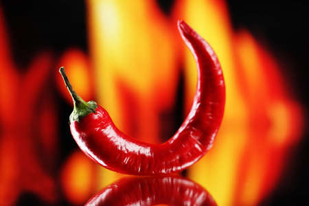 Red hot chili pepper on fire background photo