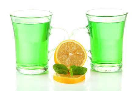Two transparent cups of green tea and lemon isolated on white photo