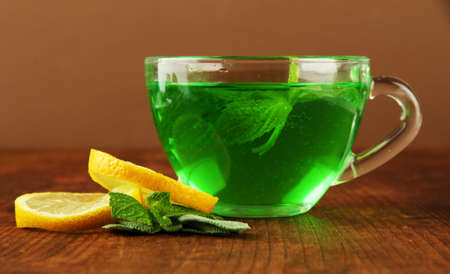 Transparent cup of green tea with lemon and mint on table on brown background photo