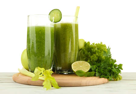 Glasses of green vegetable juice on wooden table on white background photo