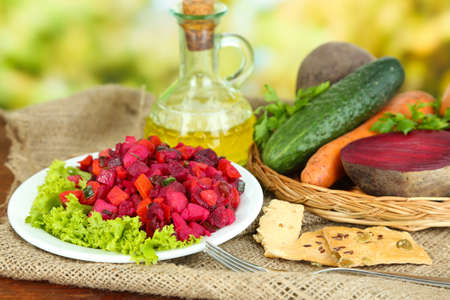 Beet salad on plate on sackcloth on wooden table on nature background Stock Photo - 22969057