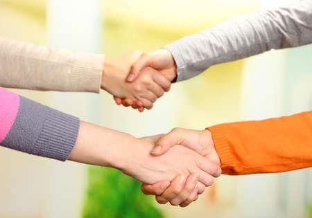manos estrechadas: Apretones de manos en el fondo brillante