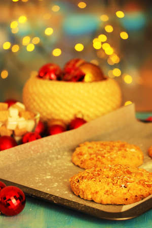 Process of making New Year cookies on Christmas lights background photo