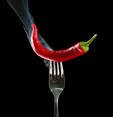 Red hot chili pepper  on fork, isolated on black Imagens