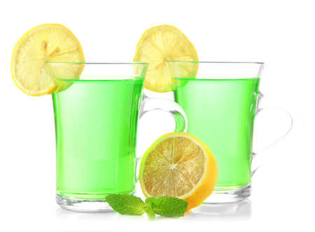 Two transparent cups of green tea with mint and lemon isolated on white photo