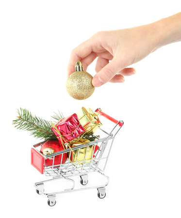 Hand and Christmas gifts in shopping trolley, isolated on white photo
