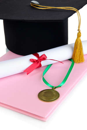 Medal for achievement in education with diploma, hat and notebook close up photo