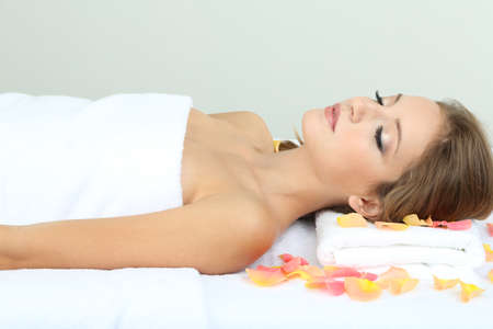 Beautiful young woman on massage table in cosmetic salon close up photo