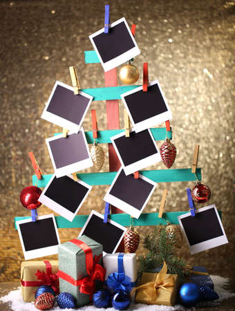 Wooden hand made fir tree with empty photo paper and Christmas decor on shiny background photo
