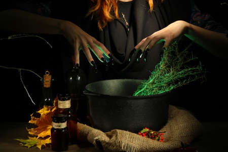 Witch in scary Halloween laboratory on dark color background photo