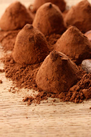 comfit: Chocolate truffles and cocoa, on wooden background Stock Photo