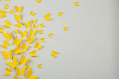 amorousness: Paper yellow butterflies fly on wall in different directions