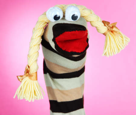 Cute sock puppet on pink background photo