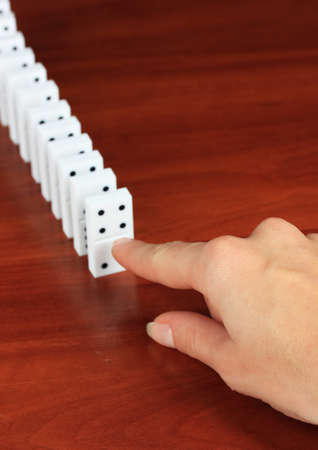 Hand pushing dominoes on wooden background photo
