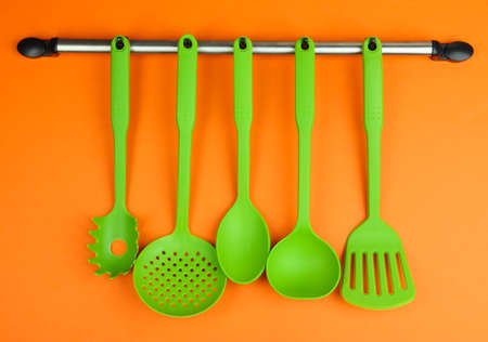 Plastic kitchen utensils on silver hooks on orange background photo