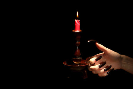 Hand with candle , isolated on black photo