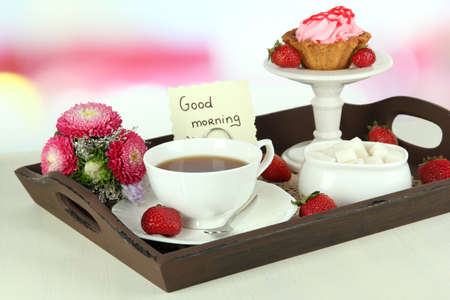 Cup of tea with cakes on wooden tray on table in room  photo