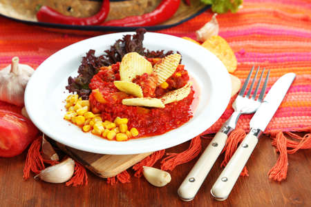 Chili Corn Carne - traditional mexican food, on white plate, on napkin, on wooden background photo