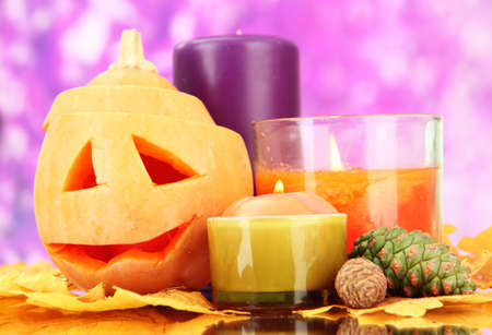 Composition for Halloween with pumpkin and candles on purple background photo