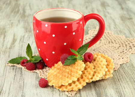 cup of tea: Cup of tea with cookies and raspberries on table close-up