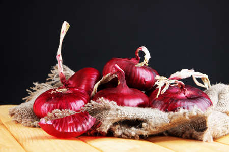 crimean: Fresh red onions on burlap on black background